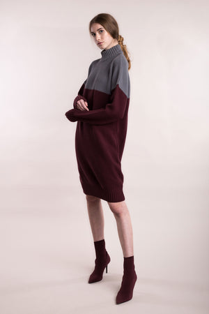 The model wears a grey and burgundy, sustainable organic cotton, knitted double-colour dress, side view.
