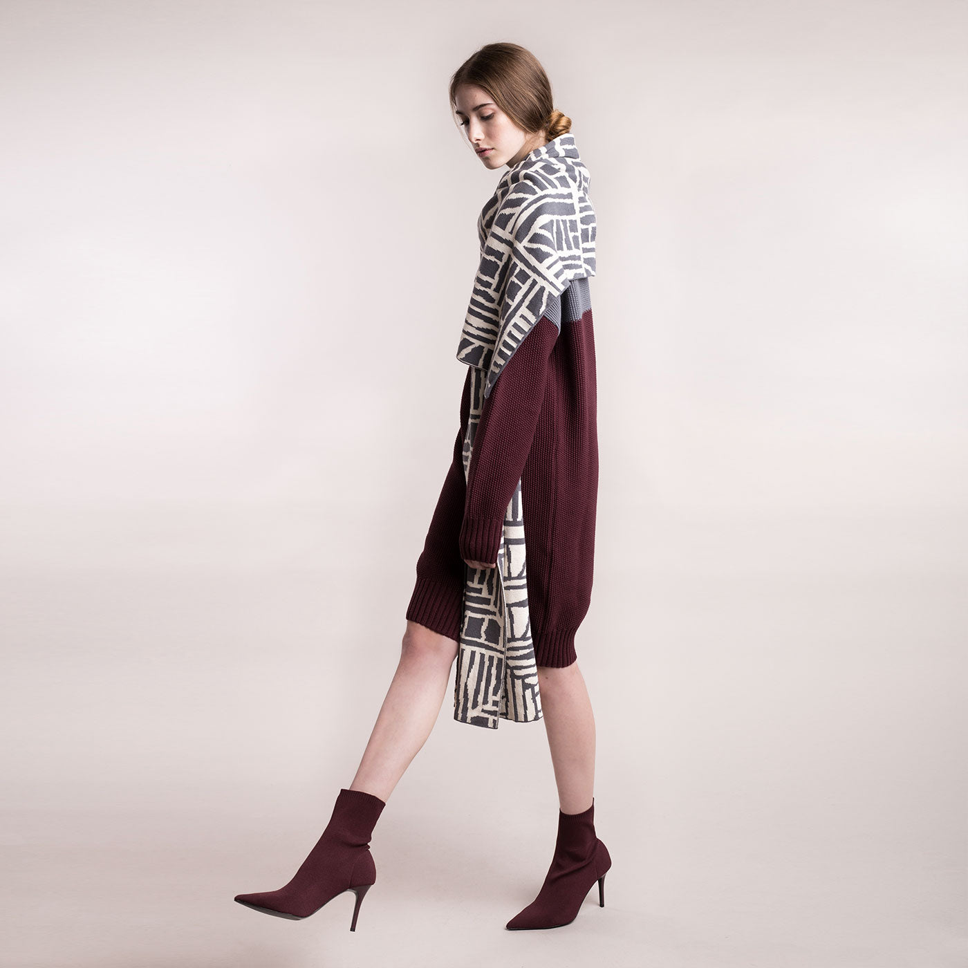 The model wears a grey and burgundy, sustainable organic cotton, knitted double-colour dress, with a scarf.