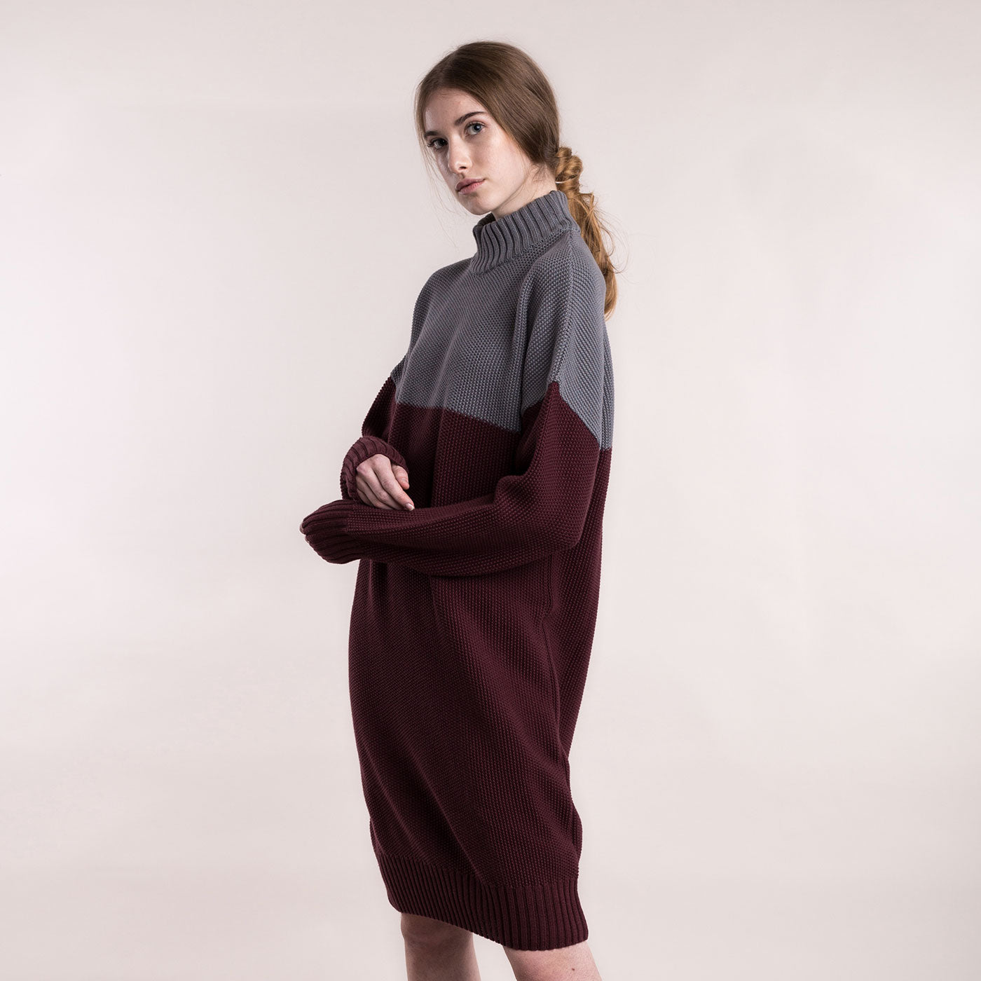 The model wears a grey and burgundy, sustainable organic cotton, knitted double-colour dress, side view close up.