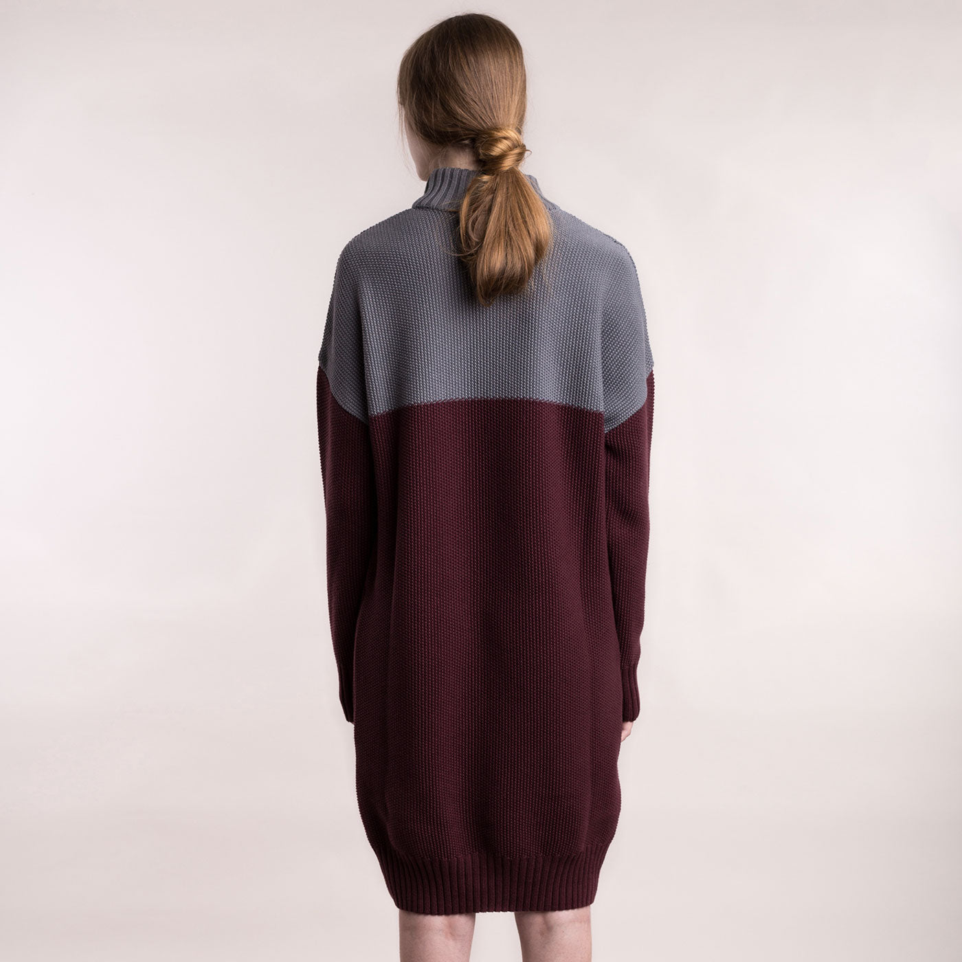 The model wears a grey and burgundy, sustainable organic cotton, knitted double-colour dress, back view.