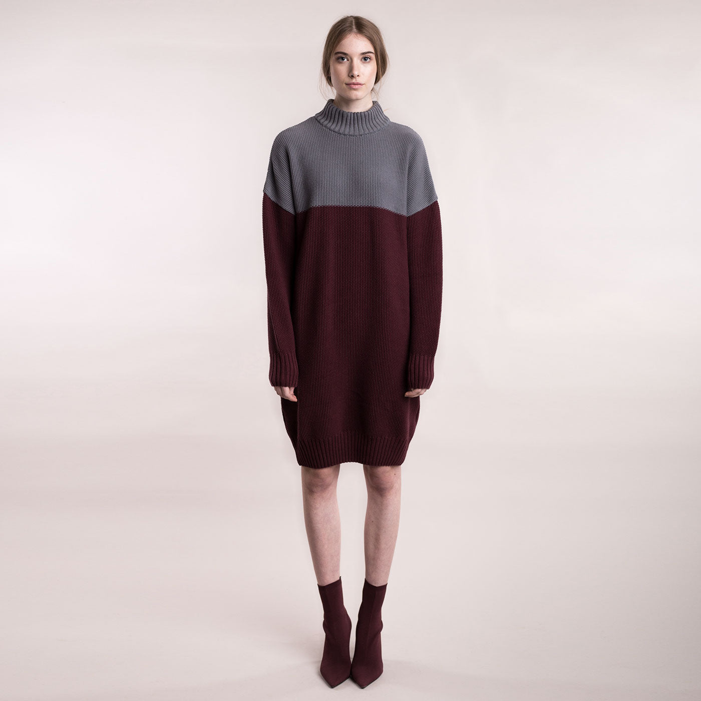 The model wears a grey and burgundy, sustainable organic cotton, knitted double-colour dress, frontal view.