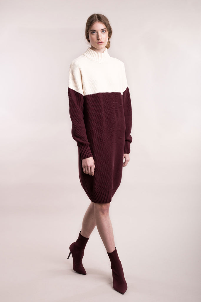 The model wears a cream and burgundy, sustainable organic cotton, knitted double-colour dress.