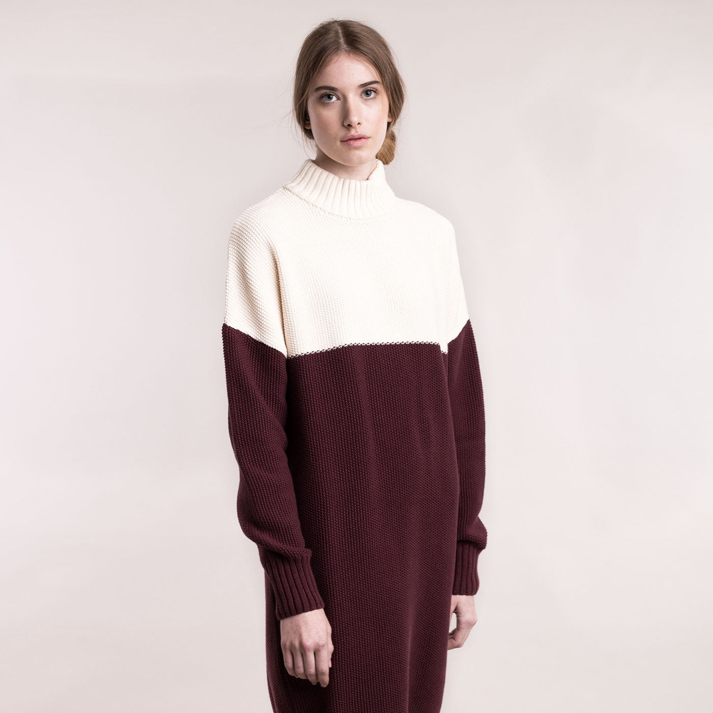 The model wears a cream and burgundy, sustainable organic cotton, knitted double-colour dress., frontal view.