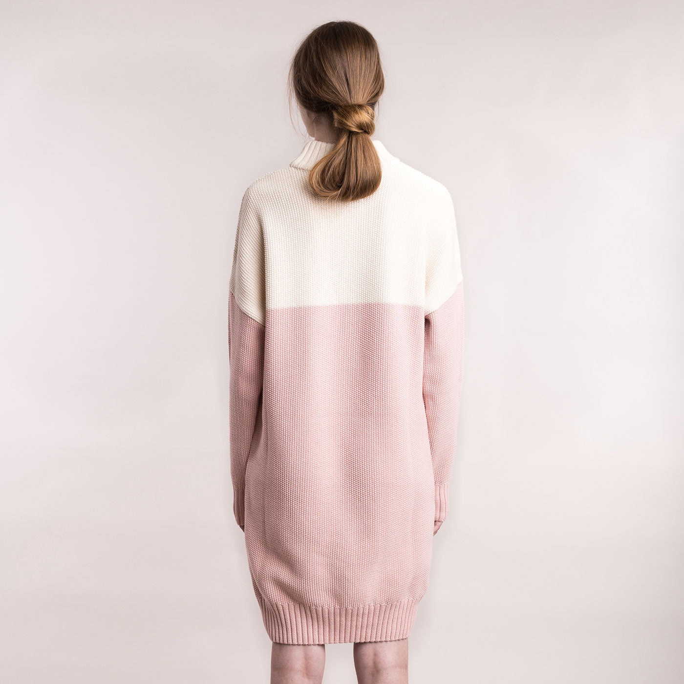 The model wears a cream and dusty pink, sustainable organic cotton, knitted double-colour dress, back view.