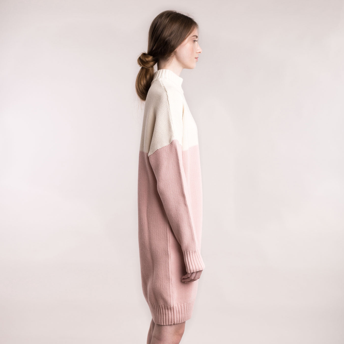 The model wears a cream and dusty pink, sustainable organic cotton, knitted double-colour dress, side view.