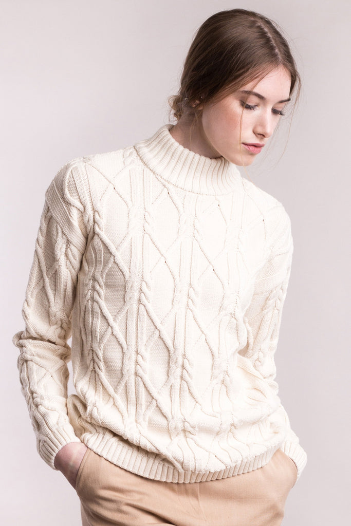 The model wears a cream sustainable organic cotton knitted aran pullover with high neck, frontal view.