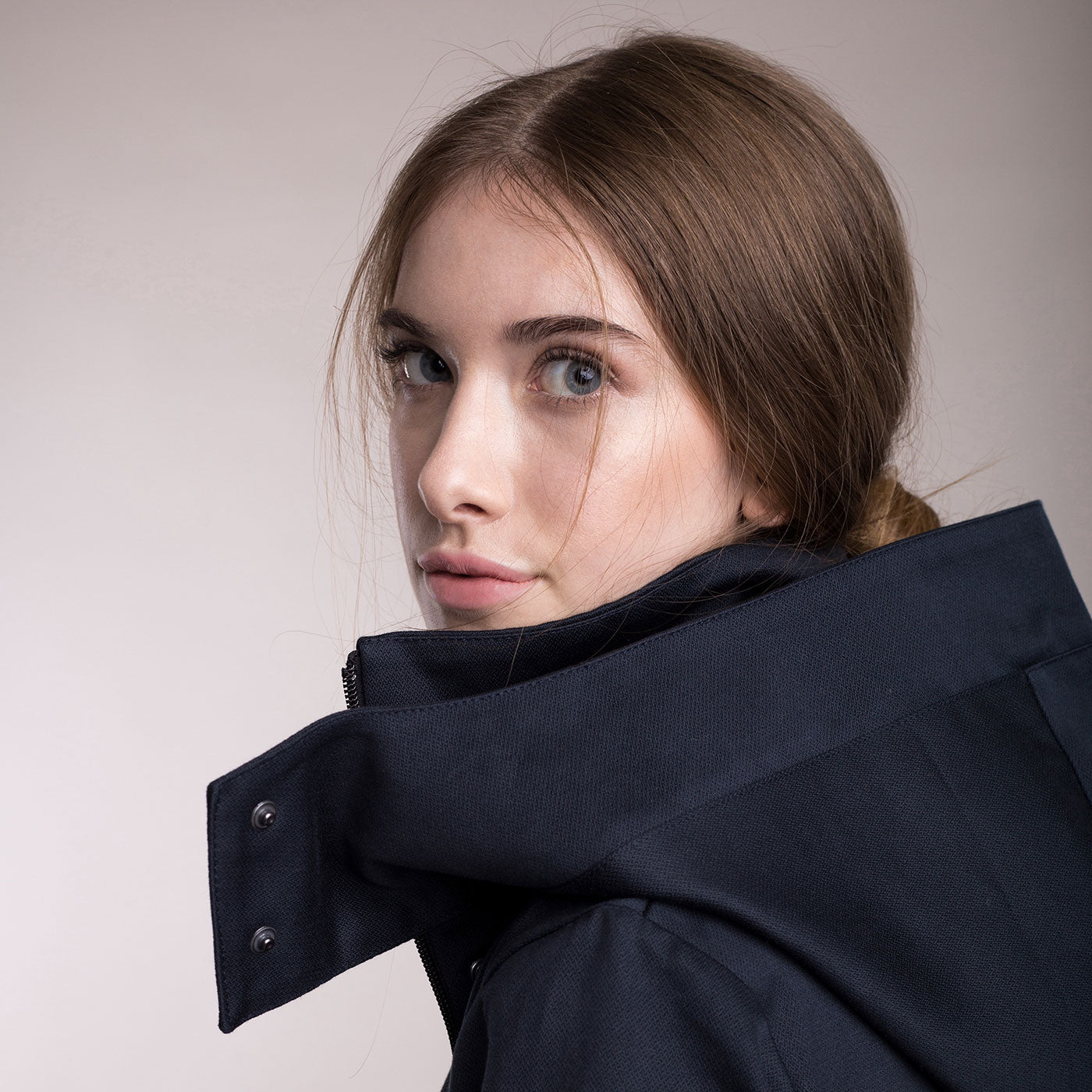 The model wears a dark blue sustainable organic cotton hooded water-resistant coat, detail hood.