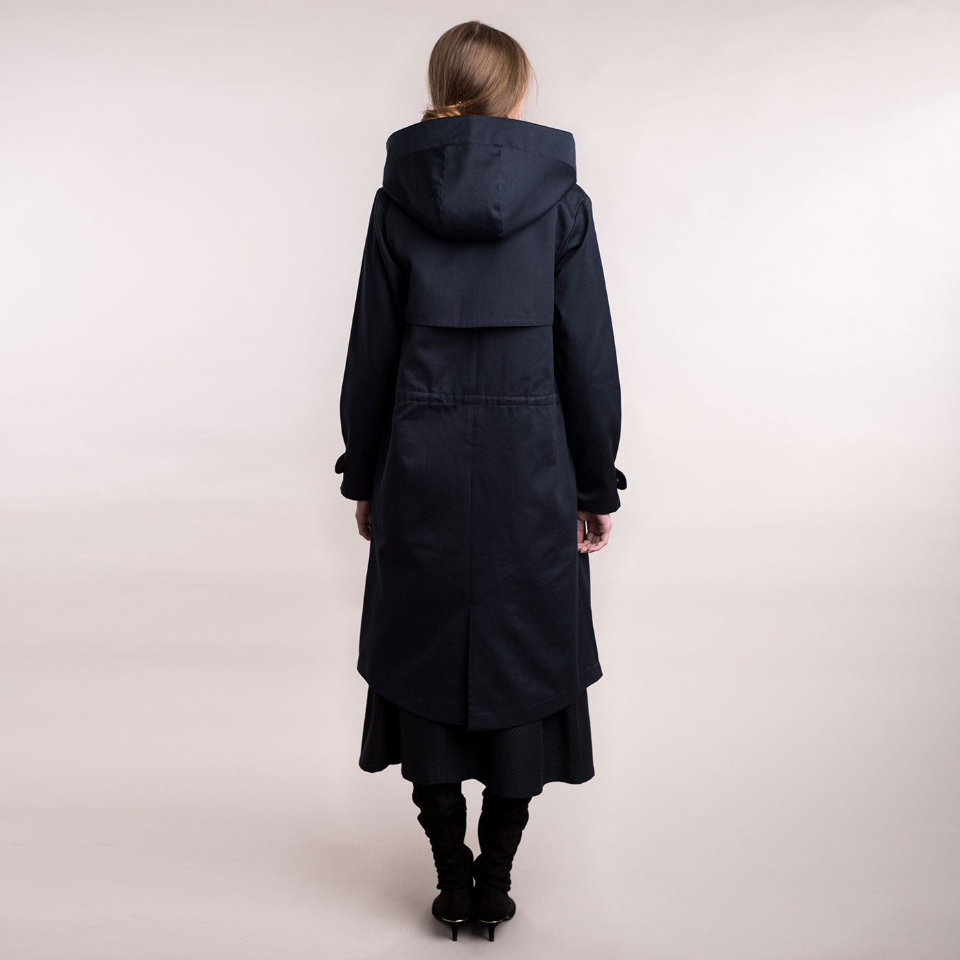 The model wears a dark blue sustainable organic cotton hooded water-resistant coat, back view.