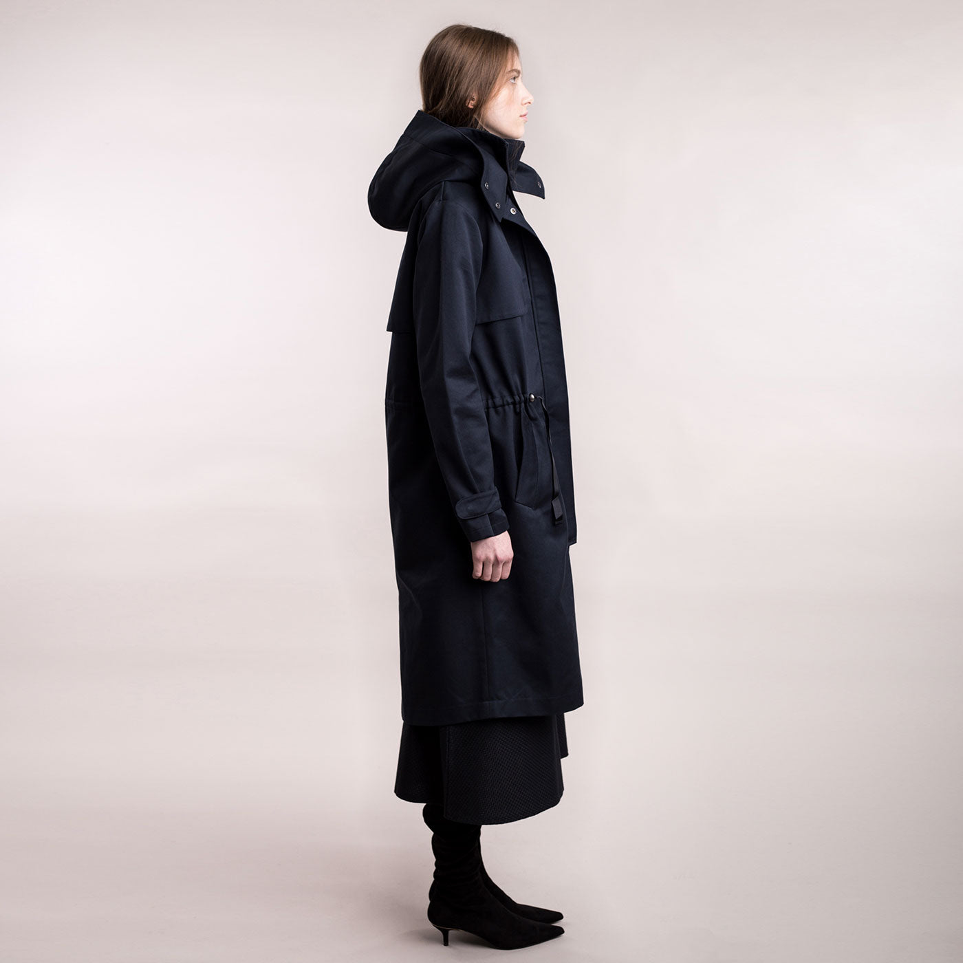 The model wears a dark blue sustainable organic cotton hooded water-resistant coat, side view.