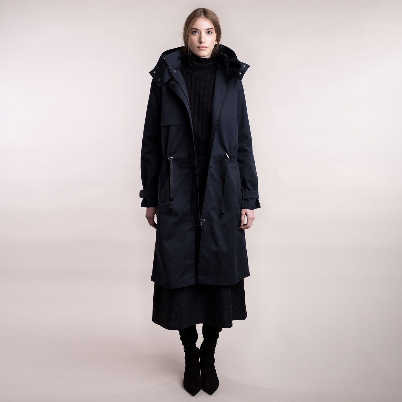 The model wears a dark blue sustainable organic cotton hooded water-resistant coat, frontal view.