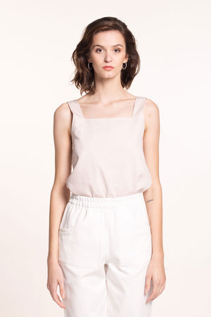 The model wears a rose-beige, sustainable, organic cotton, wide straps top and white pants.