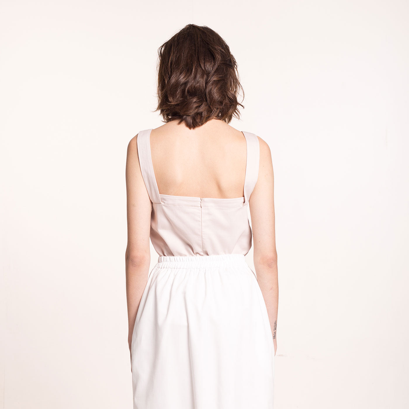 The model wears a rose-beige, sustainable, organic cotton, wide straps top, back view.