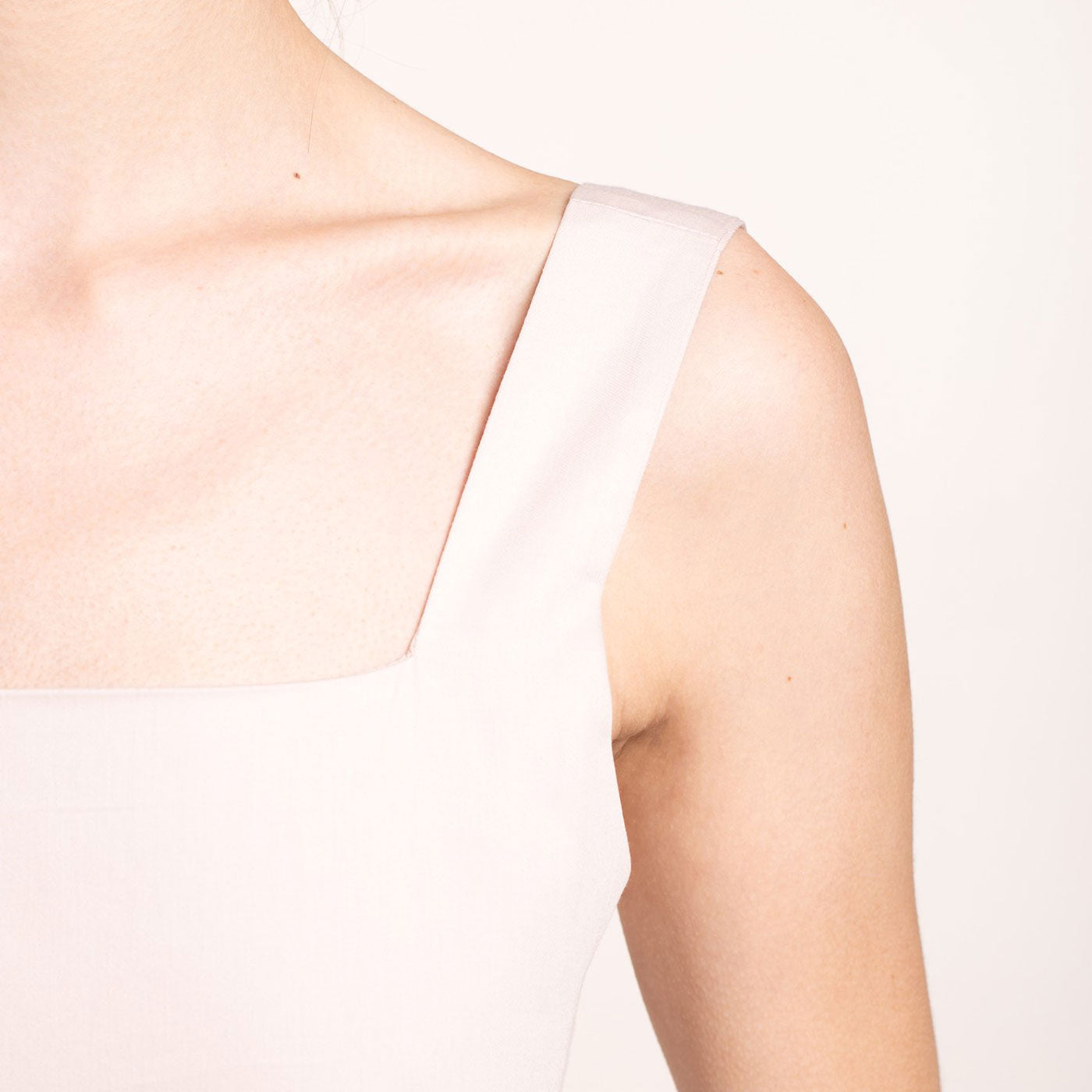 The model wears a rose-beige, sustainable, organic cotton, wide straps top, detail strap.