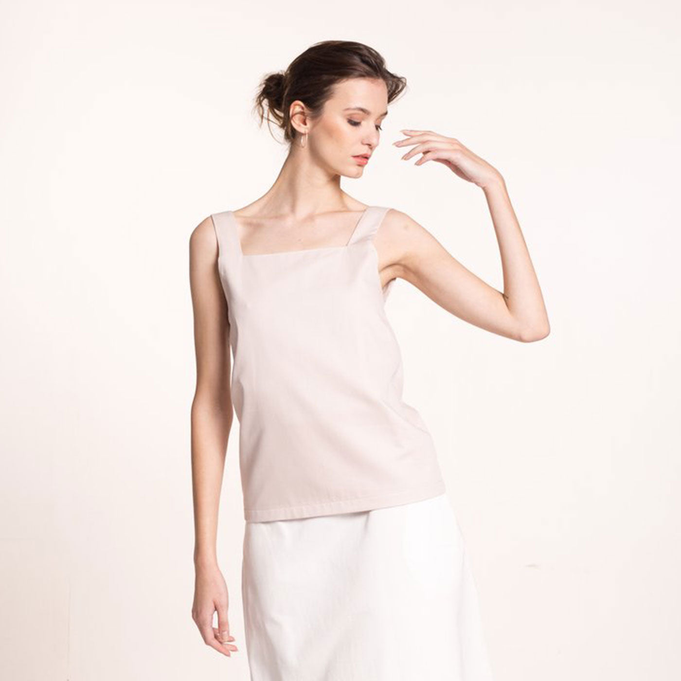 The model wears a rose-beige, sustainable, organic cotton, wide straps top and a white skirt.