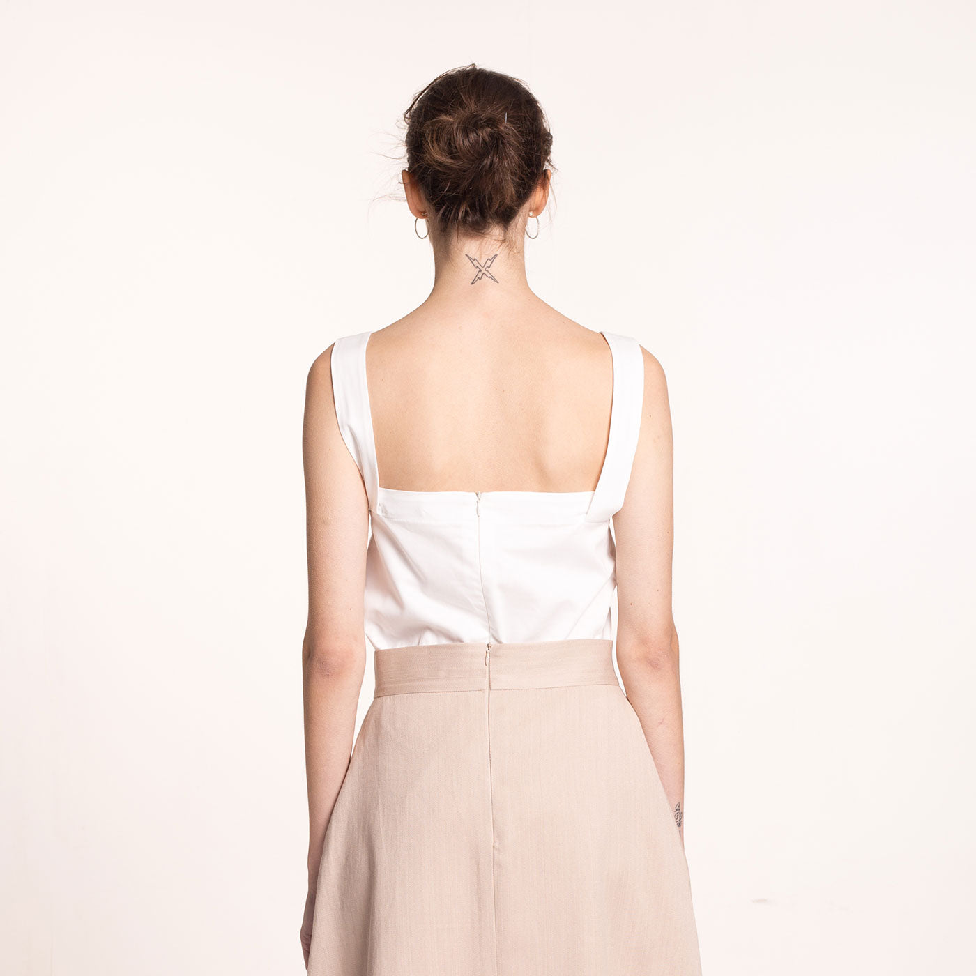 The model wears a white, sustainable, organic cotton, wide straps top, back view.