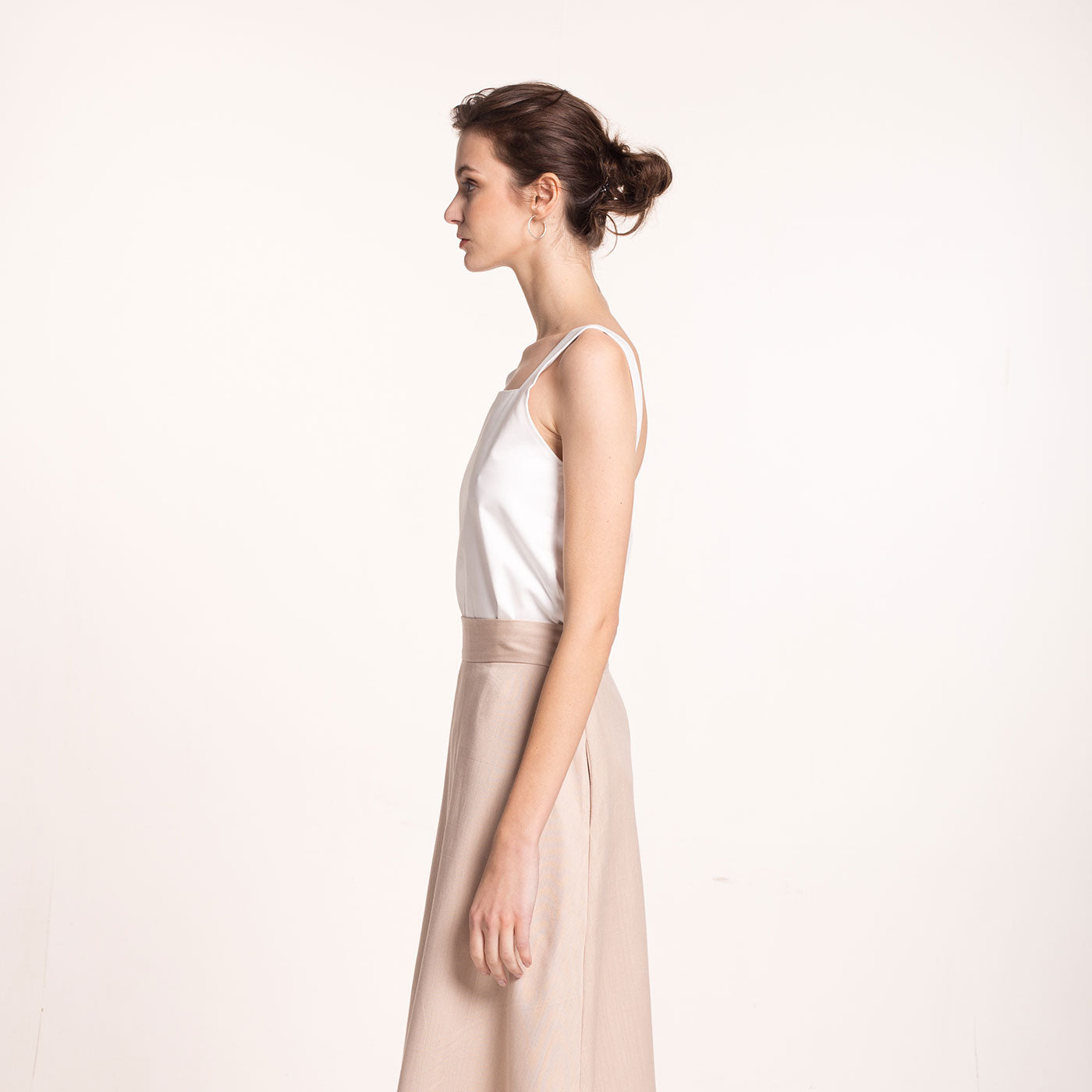 The model wears a white, sustainable, organic cotton, wide straps top, side view.