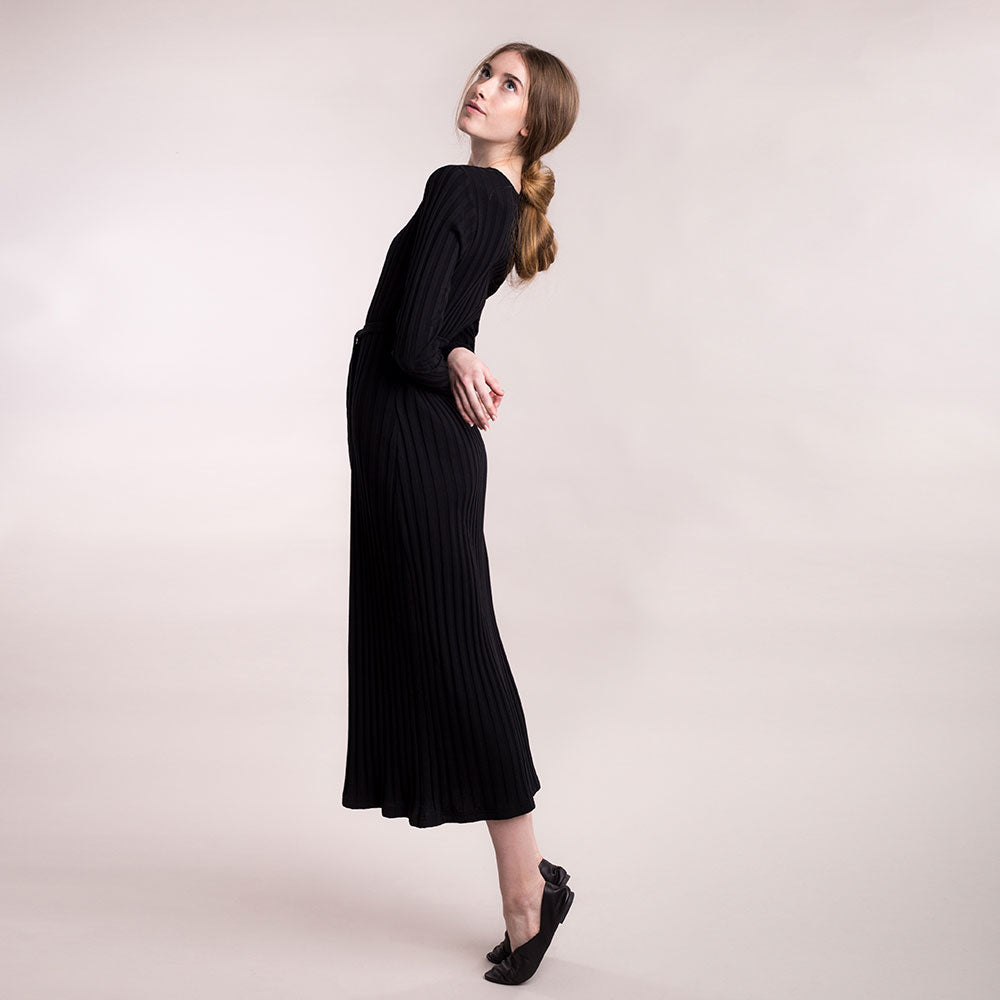 The model wears black, sustainable organic cotton, wide-rib long dress, side view.