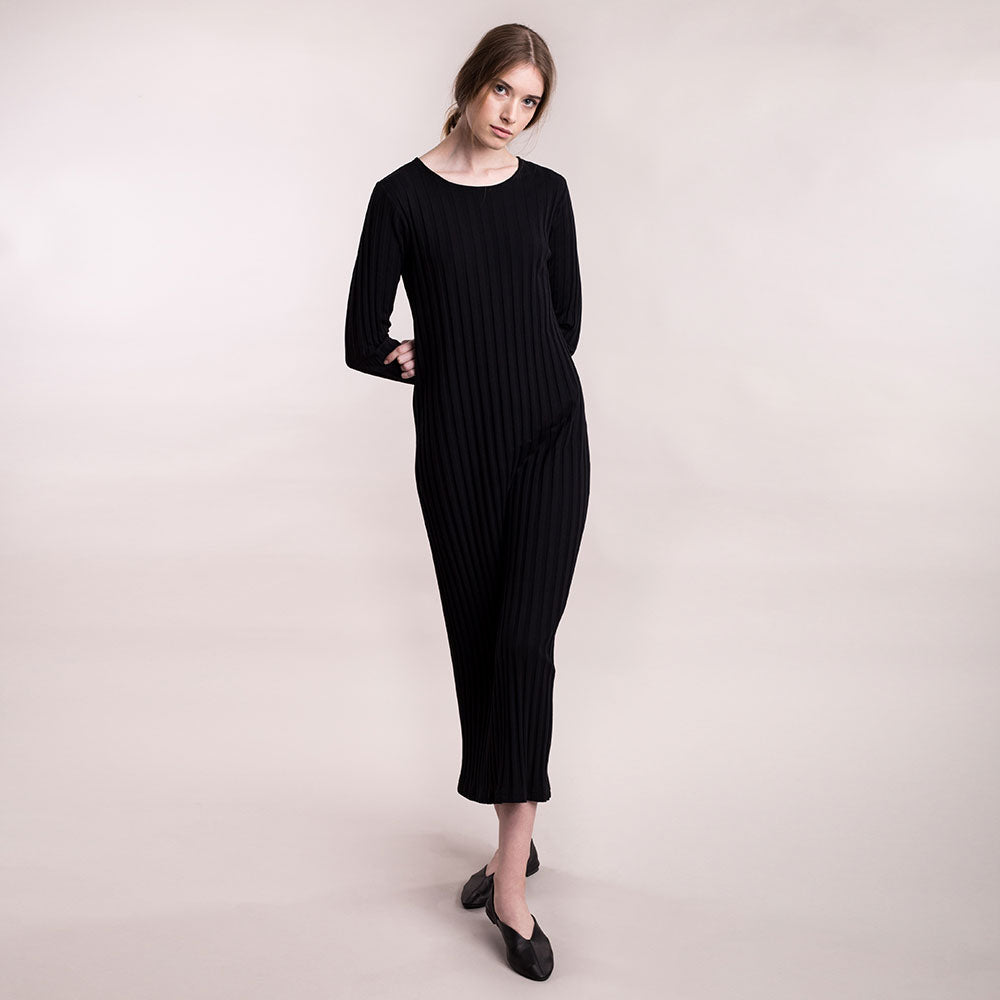 The model wears black, sustainable organic cotton, wide-rib long dress, front view.