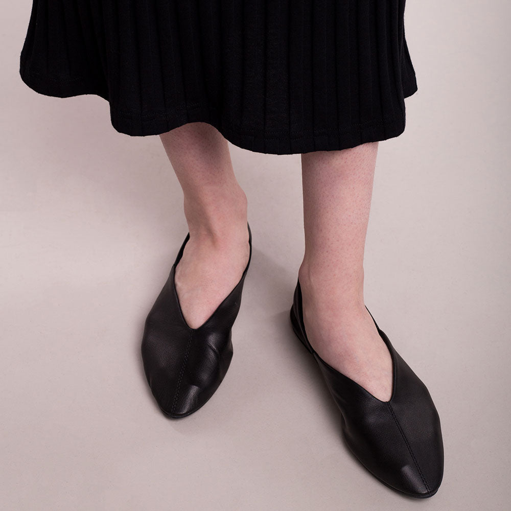 The model wears black, sustainable organic cotton, wide-rib long dress, close up feet.