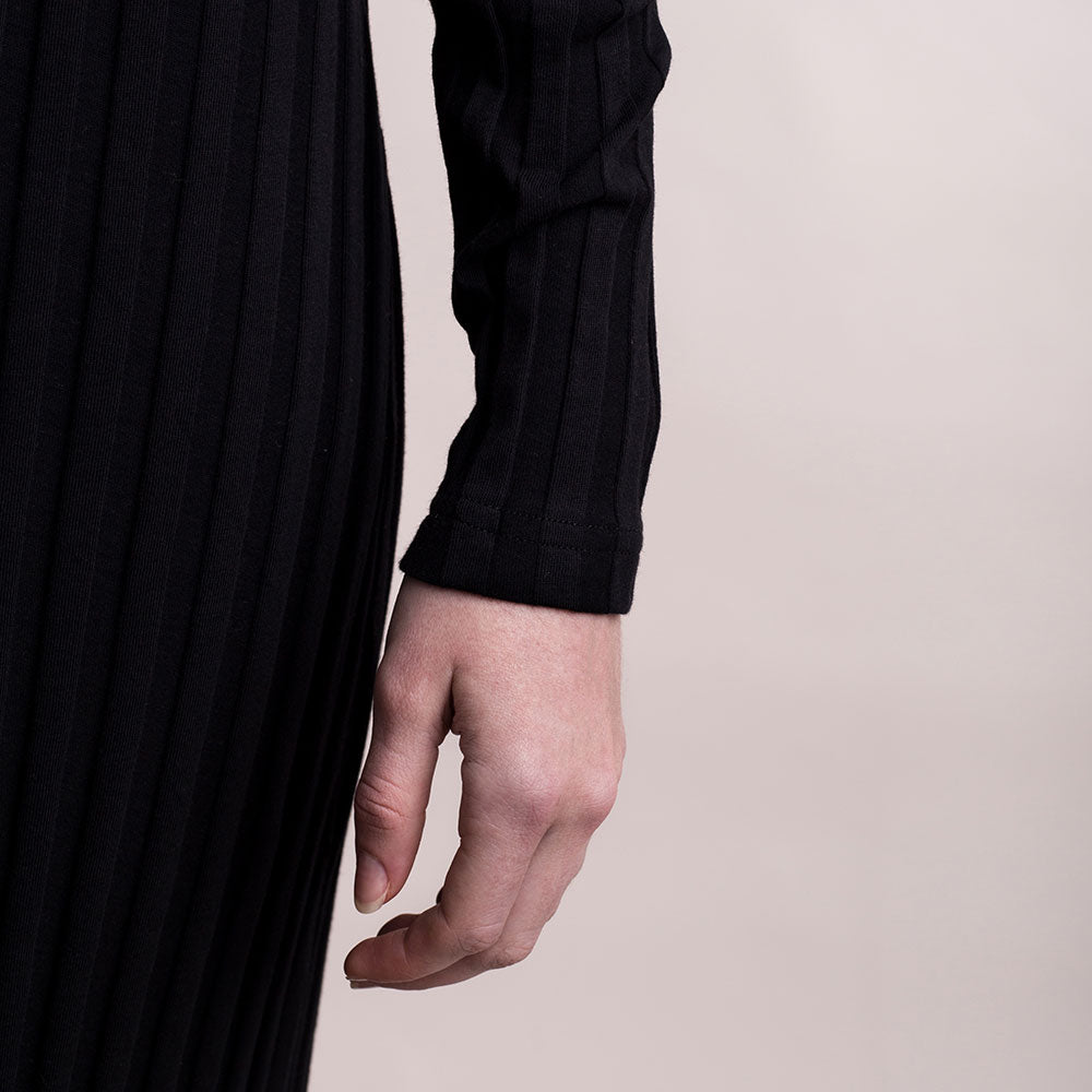 The model wears black, sustainable organic cotton, wide-rib long dress, detail sleeve.