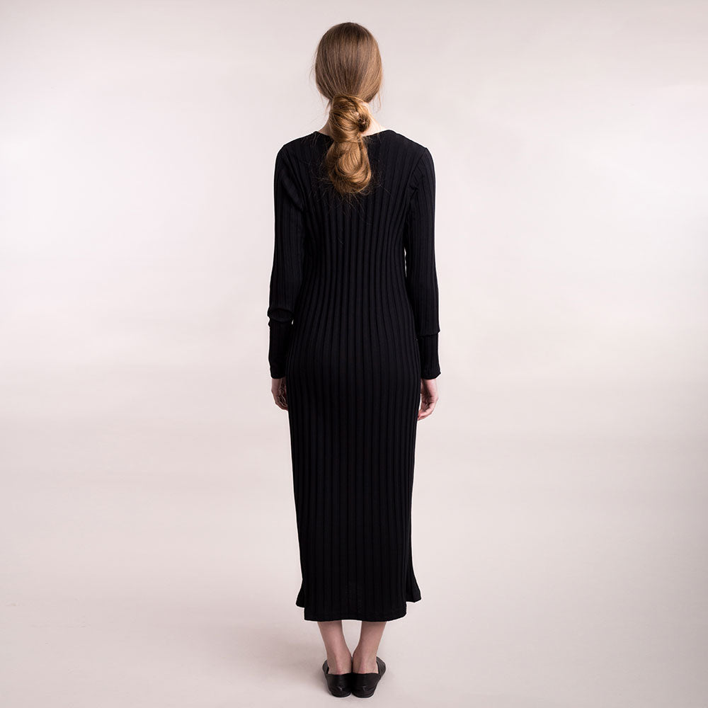 The model wears black, sustainable organic cotton, wide-rib long dress, back view.