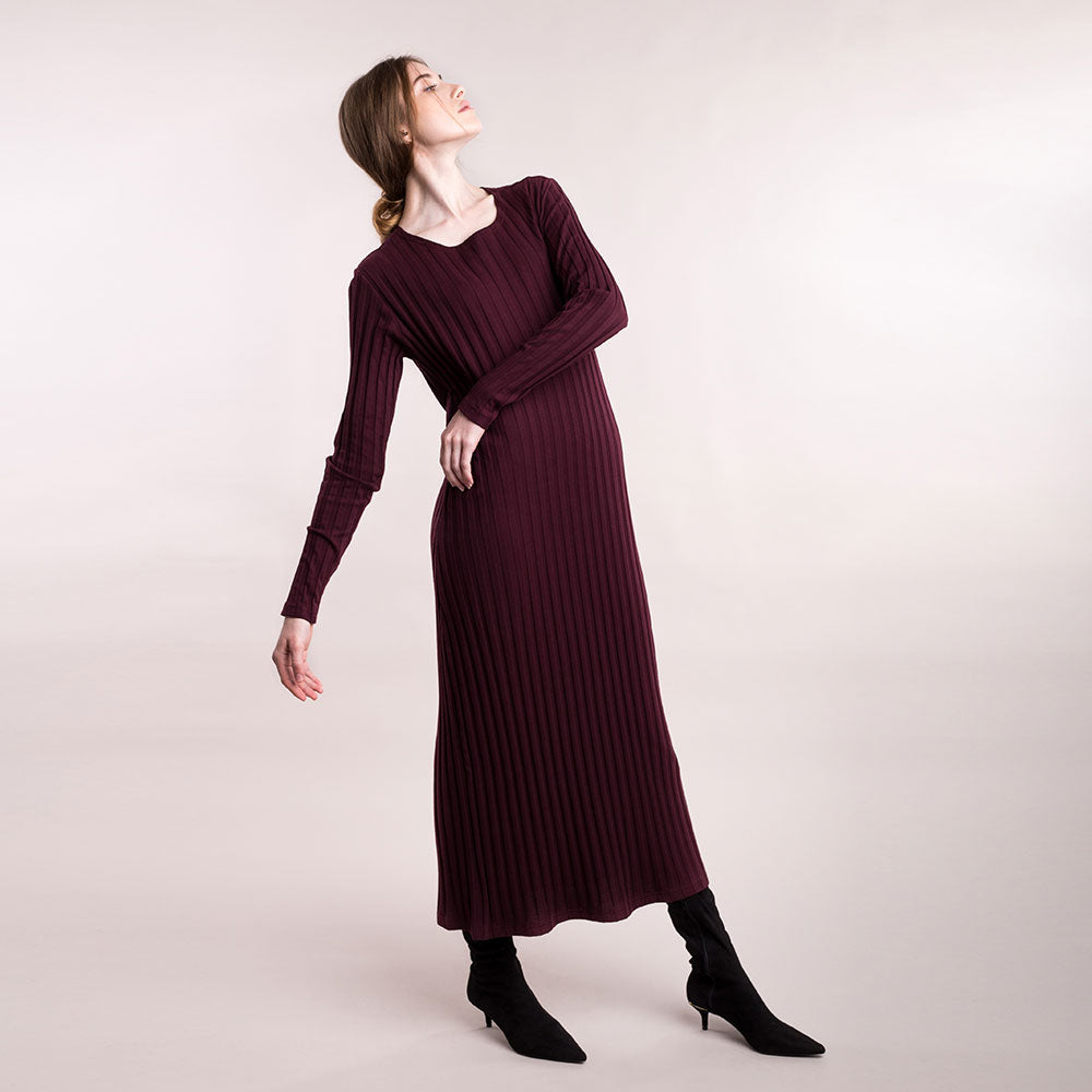 The model wears burgundy, sustainable organic cotton, wide-rib long dress.