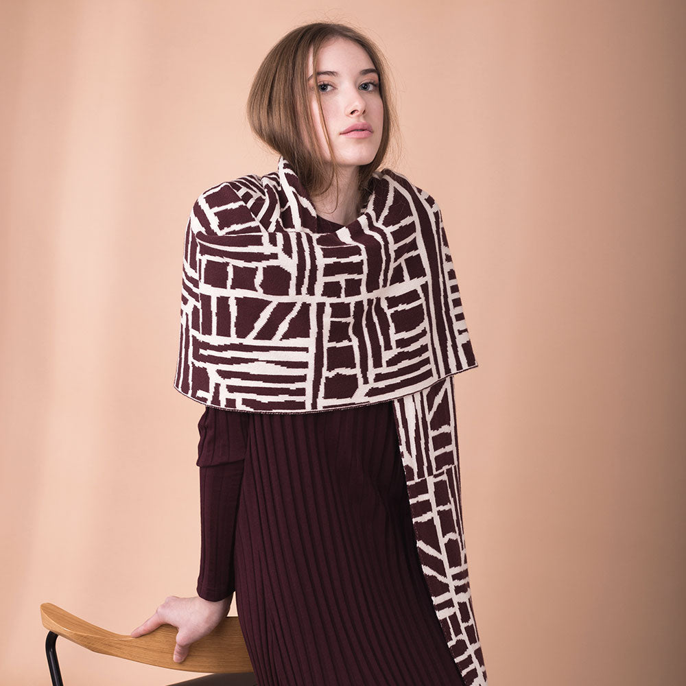 The model wears burgundy, sustainable organic cotton, wide-rib long dress, with a scarf.