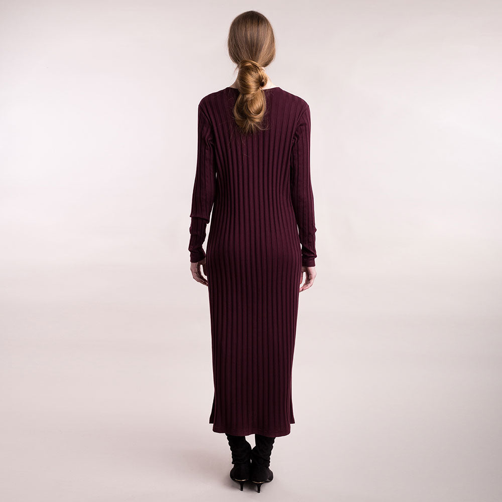 The model wears burgundy, sustainable organic cotton, wide-rib long dress, back view.