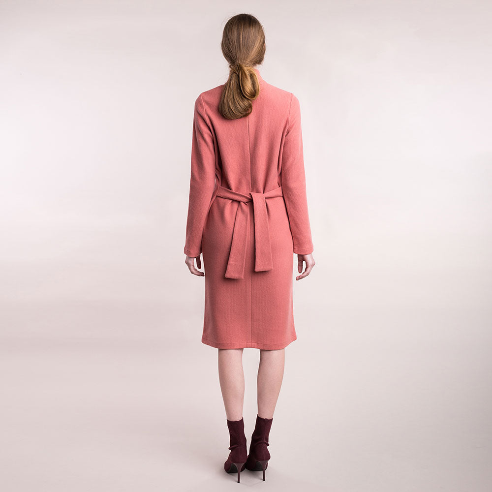 The model wears a peach, sustainable organic cotton, soft corduroy high-neck dress, back view.