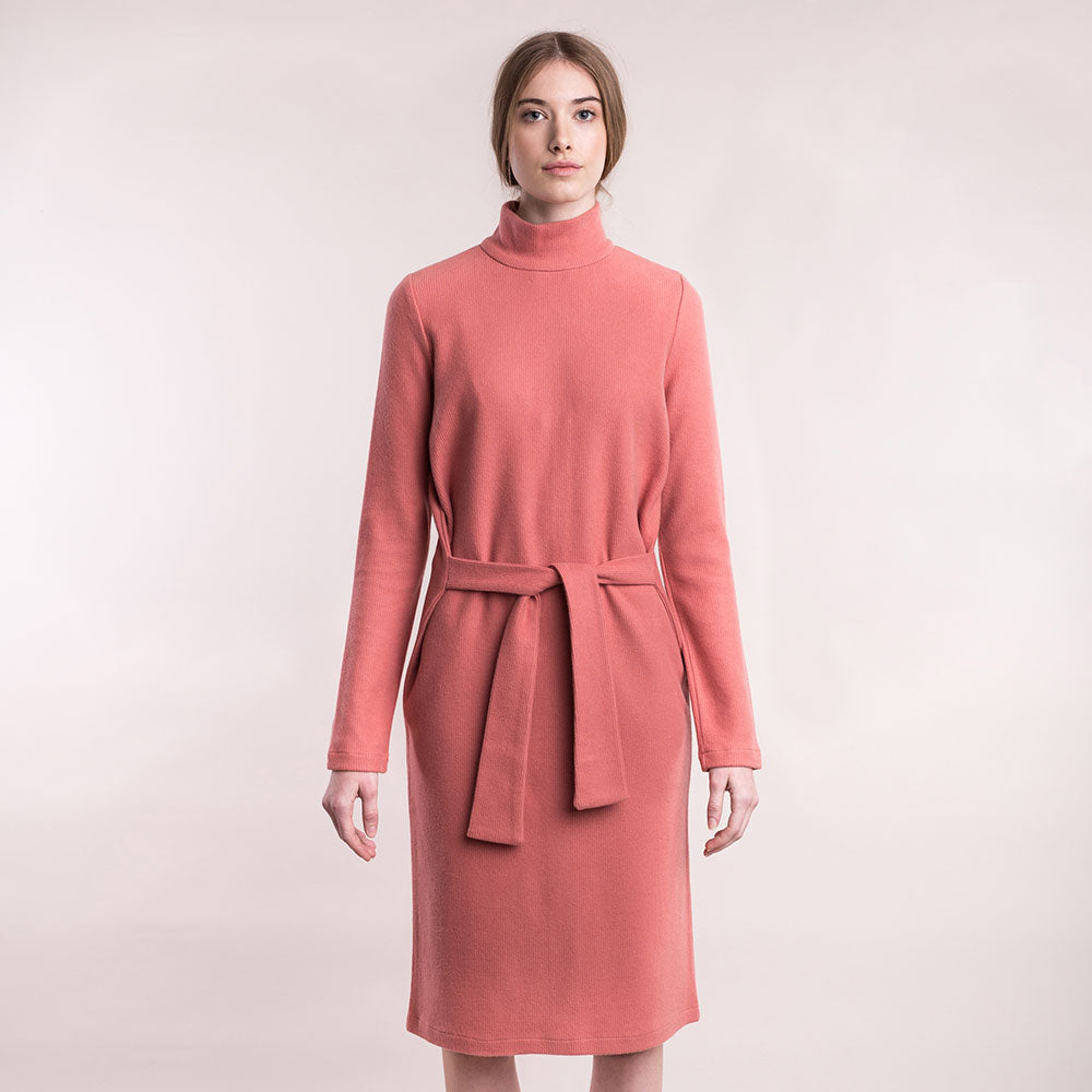 The model wears a peach, sustainable organic cotton, soft corduroy high-neck dress.