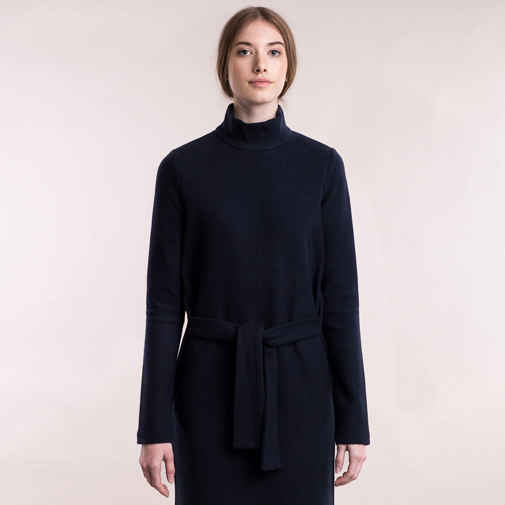 The model wears a dark blue, sustainable organic cotton, soft corduroy high-neck dress, front view..