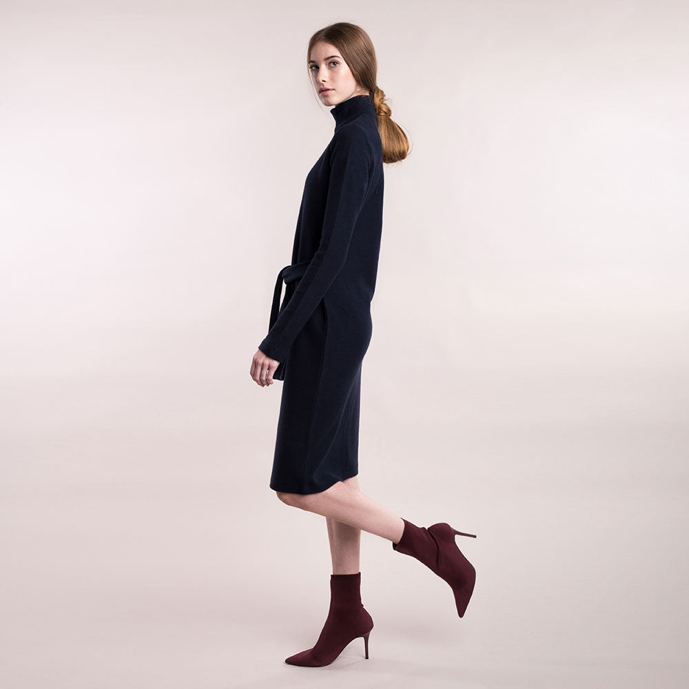 The model wears a dark blue, sustainable organic cotton, soft corduroy high-neck dress, side view..
