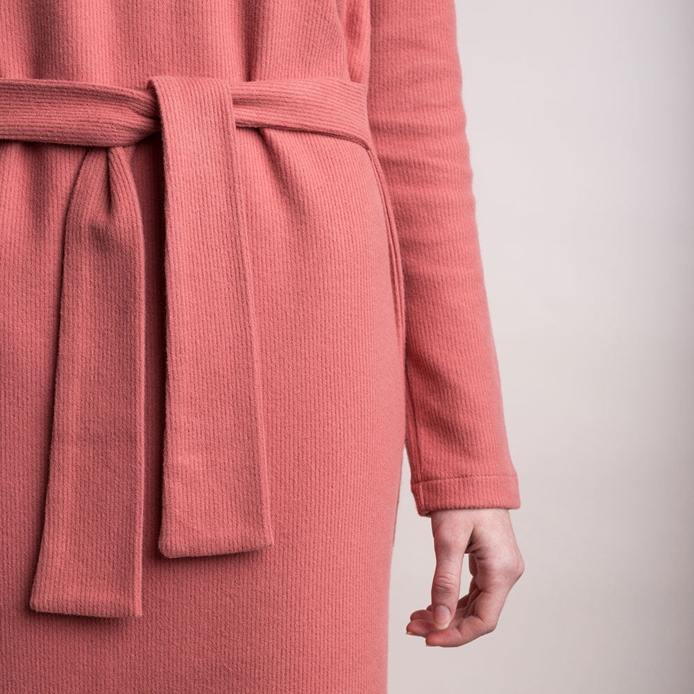The model wears a peach, sustainable organic cotton, soft corduroy high-neck dress, detail belt waist.