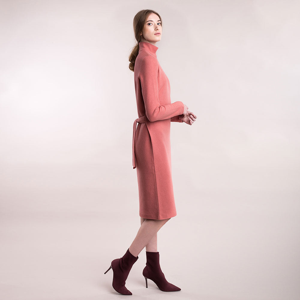 The model wears a peach, sustainable organic cotton, soft corduroy high-neck dress, side view.