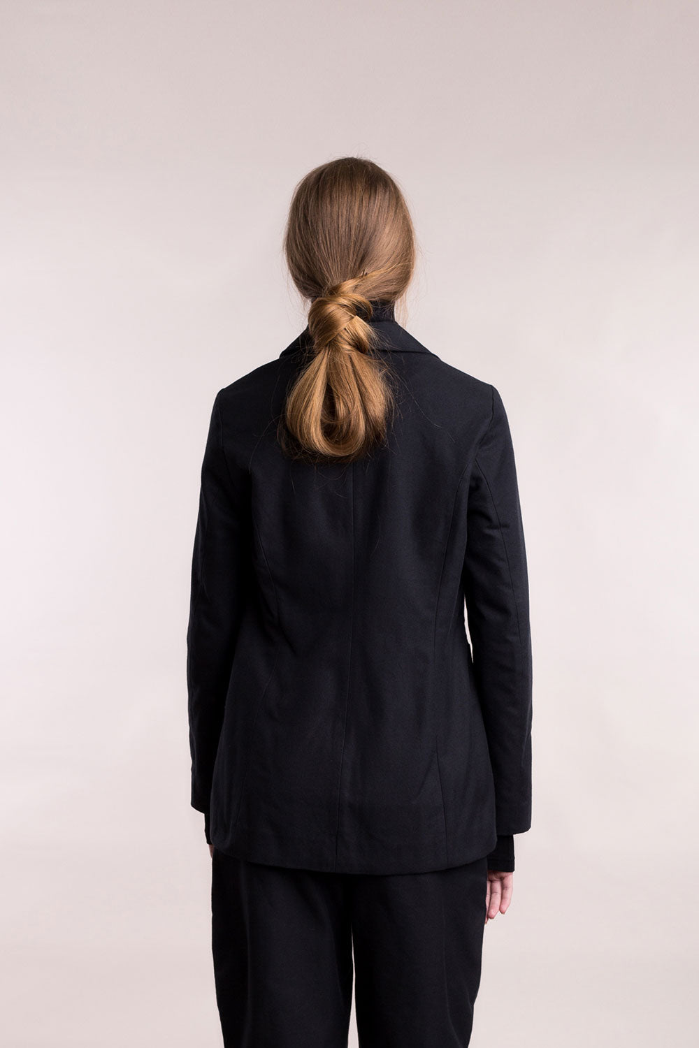 The model wears a black, sustainable, organic cotton, back view.