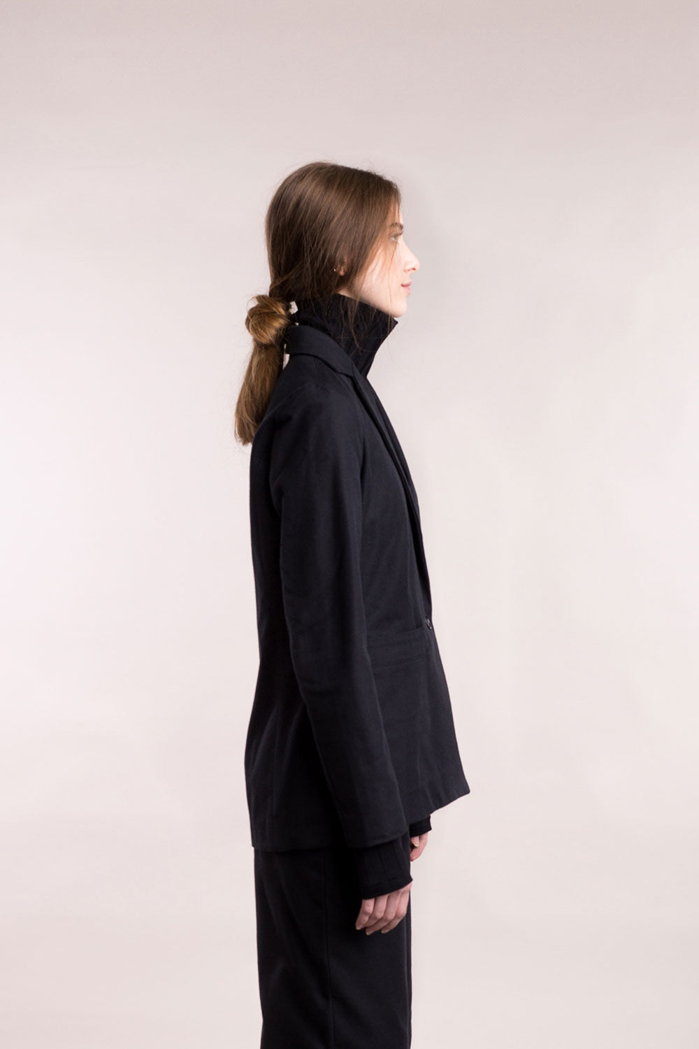 The model wears a black, sustainable, organic cotton, tailored jacket, side view.