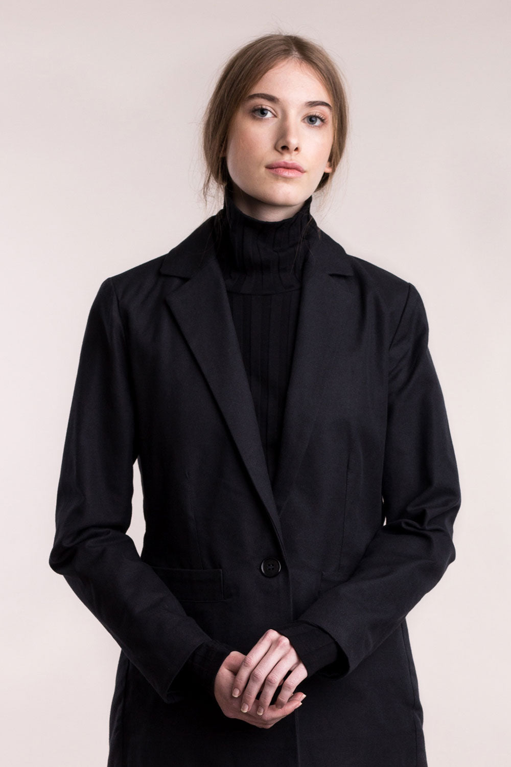 The model wears a black, sustainable, organic cotton, tailored jacket, front view.
