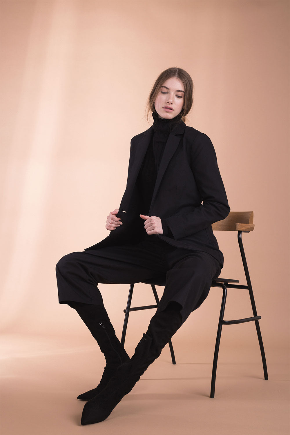 The model wears a black, sustainable, organic cotton, tailored jacket and sits on a chair.
