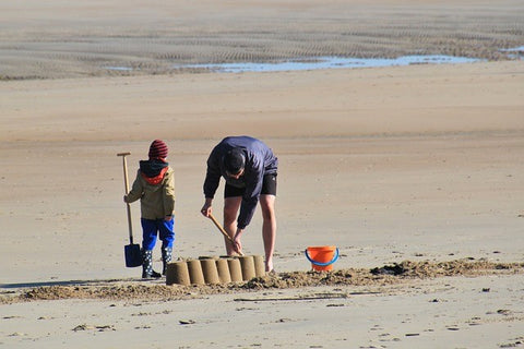 dad and child building sandcastle