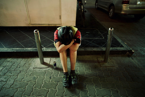 Cyclist with her head on her knees after her first race