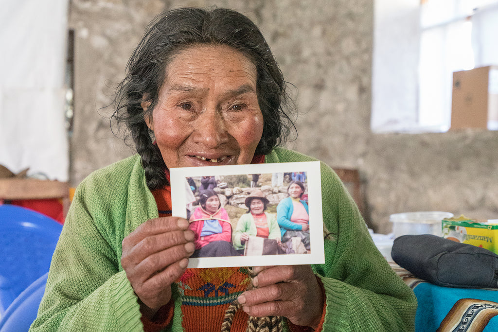 a south american lady holding a portrait that Federico took of her and her friends
