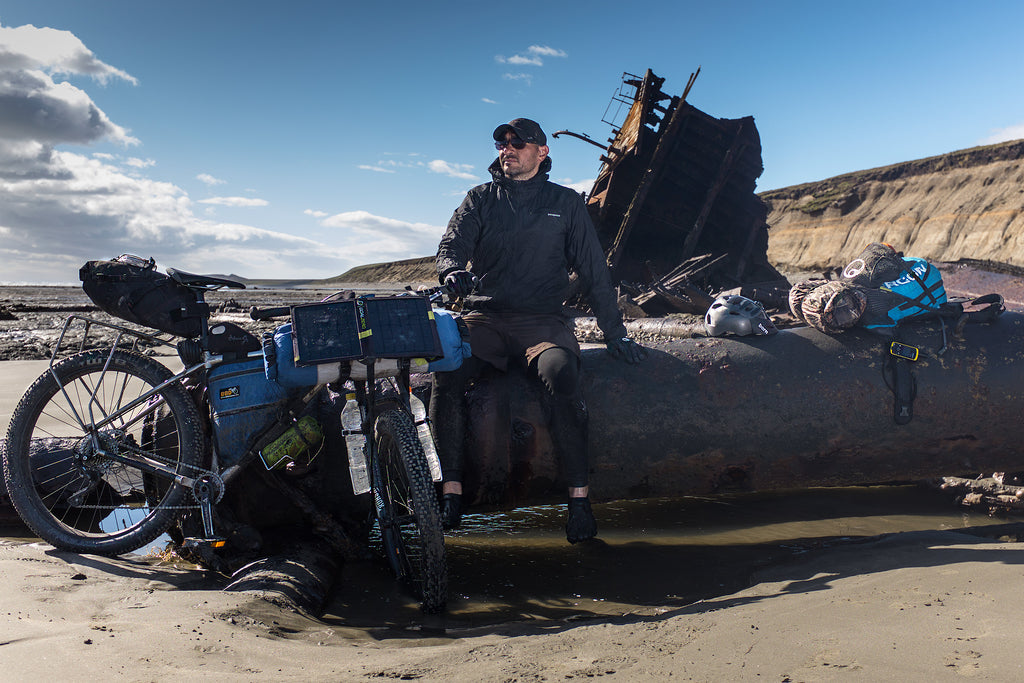 Federico sat on a beached shipwreck with his cycling rig and equipment