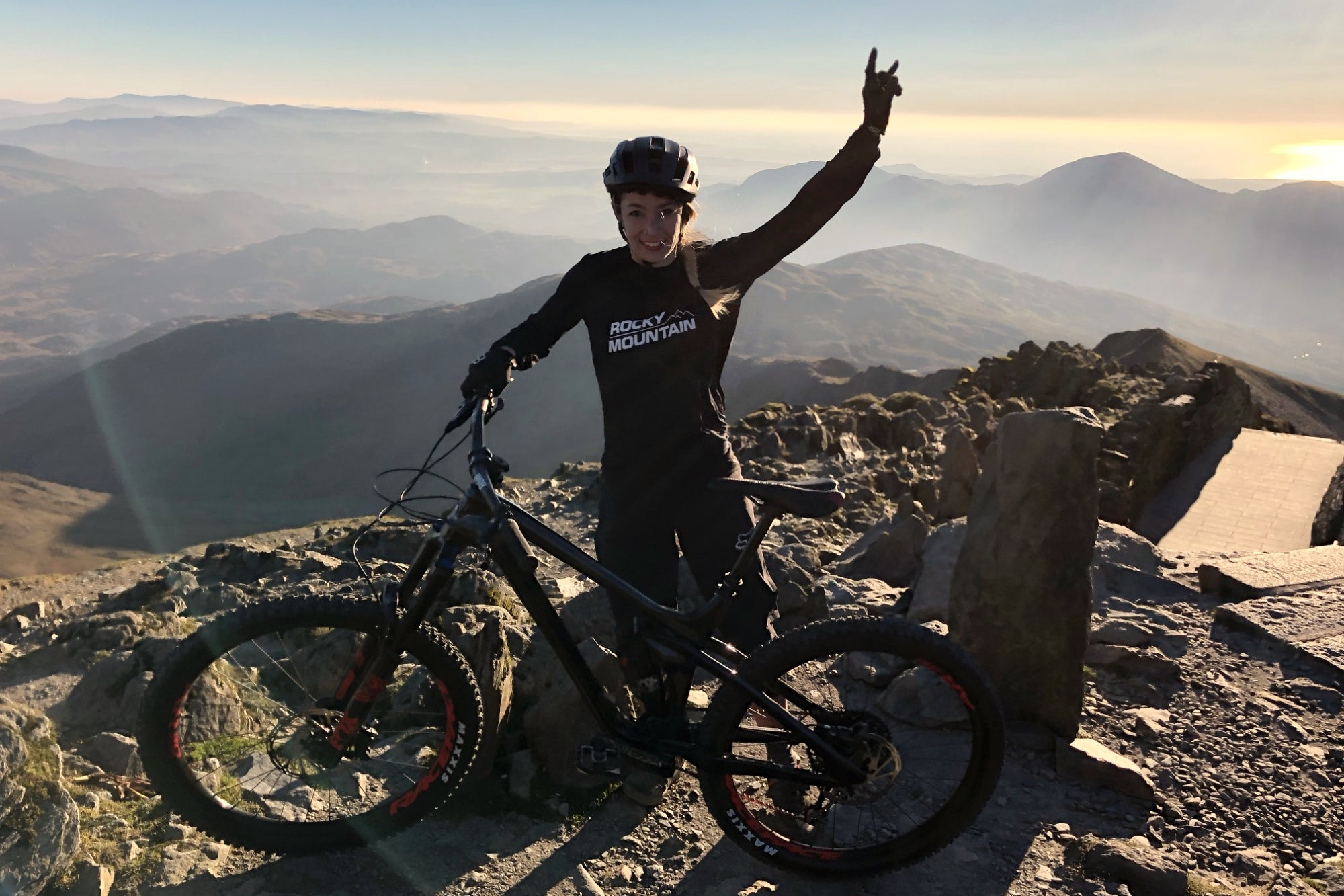 Becci Skelton with arms in the air at the top of a mountain