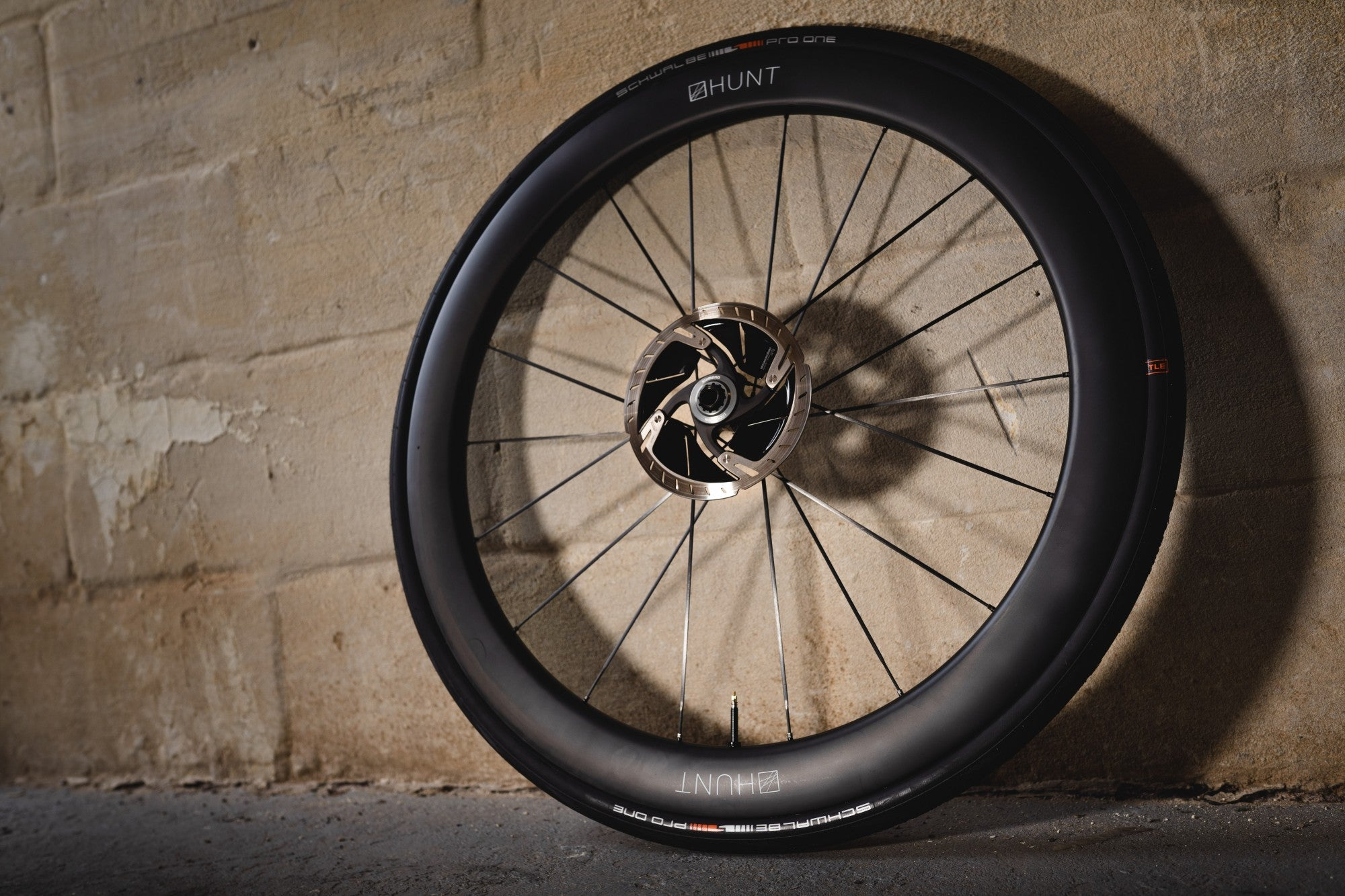 The Hunt UD 44/54 Carbon Spoke Disc Wheel against a wall