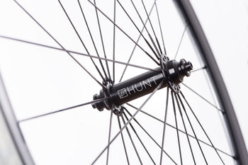 <h1>Hubs</h1><i>The hubs on the Race Aero SuperDura benefit from larger 12mm front and 15mm rear axles. This combined with them being machined from hard and strong 7075-T6 heat treated alloy means that they easily withstand the higher loads created by larger riders. Plus the cold forged then CNC machined hub shell means the metal grain structure is ideally aligned to handle the high spoke loads, the work hardening from the cold forging also adds extra strength.</i>