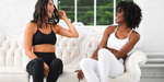 Two women in athletic gear happily chatting on a white couch