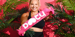 "Woman in athletic gear in front of a pink background and palm leaves holding a ""Booty"" sign and smiling"