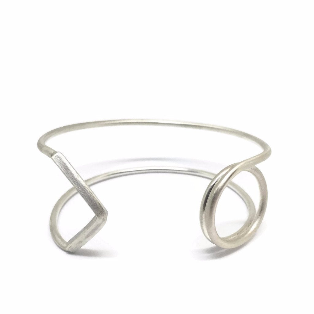 Thin silver threads are neatly wrapping your wrist, while on the edges appearing symbolic elements such as a spiral symbolizing protection, healing and energetic release and an arrowhead align in 90 degrees that symbolizes security.