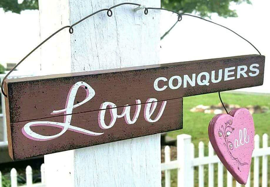LOVE CONQUERS ALL.   WOOD SIGN