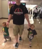 Dad wearing Jurassic Park style Twin Parenting shirt with twin toddlers.